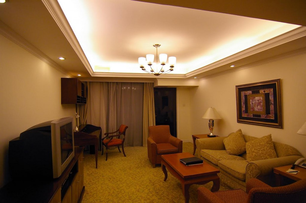 a living room in a high rise apartment at night, soft chairs, tv and settee